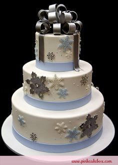 Snowflakes and a silver ribbon higlight this winter themed wedding cake