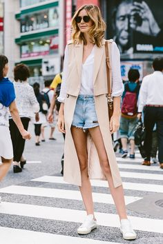 spring / summer - street style - neutral layers - summer outfits - casual outfits - beige sleeveless trench coat + deni shorts + white sneakers + white shirt + brown sunglasses + brown shoulder bag