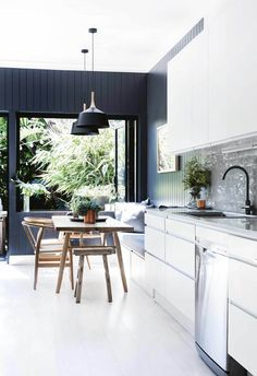 White cabinetry complements grey subway tiles in this coastal kitchen, and pair beautifully with white limewashed floor boards and a dark feature wall.