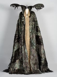 A milliner spent four weeks hand-cutting and mounting each rooster feather to the cloak. Ravenna's cloak in Snow White and the Huntsman. Costume design by Colleen Atwood.