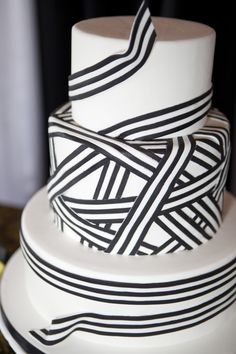 Bold graphic lines of black and white sugar ribbon wrapped around a 3-tier cake for a modern, unique look inspired by Adrey Hepburn's hat in My Fair Lady.  cake by For Goodness Cakes