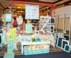 craft show fair boutique booth display. I like the stand the aprons are hanging from.
