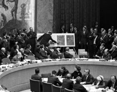 Army Col. David Parker uses enlarged aerial photos of Soviet missile sites in Cuba to point out bases as Soviet representative Valerian Zorin and others look on at the United Nations in 1962