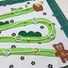 Page 5 in our Busy Book series is a fun game of Bear and Honey Pot! Create a pathway to help Bear follow the bees to the Honey Pot. Find the tutorial at #WeAllSew. #sewingproject #sewingtutorial #sewingforkids #busybook #quietbook