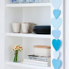 Blue heart bunting displayed beside open white wood shelving displaying books and tableware.