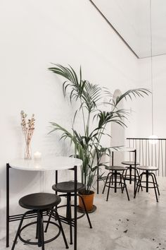"""A high/low mix: Tables with Portuguese marble tops are paired with low black stools from Ikea.""""They are discrete, just here to help,"""" Garrec says. (For something similar in the US, try the Raskog Stool.)"""