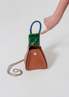 "100% Vegan Leather Brown Body with Blue and Green Trim. Detachable Silver Chain Strap. 6""L x 7""H Imported"