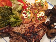 Nummies! Rosemary pork chop, steamed broccoli with butter, salad, sautéed mushrooms, and crispy potato slices with sour cream, bacon, and green onion.