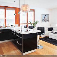 Die Wohnküche in Schwarz-Weiß besticht mit modernen Hochglanz-Oberflächen. Farblich passend gesellt sich die lederne Sofalandschaft dazu. Die modernen Design-Leuchten…