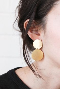 brass disc earrings on 14kt gold french ear wires. these guys stick right onto your earlobe. each pair will vary slightly due to their handmade nature. brass will age beautifully with time but can be