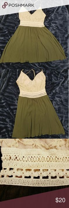 Flowy cream and olive green dress This is a very feminine little dress. The skirt hits at the thigh, you can see skin through the band, and there is a dainty floral element to the bodice. It stays in place with 2 stretchy spaghetti straps that cross in the back. The bust does have padded inserts. Papaya Dresses