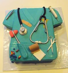 Nurse scrubs cake w/ Edible instruments - Items on cake are tweezers, stethoscope, syringe, scissors, gauze ,coban, percussion instrument, pills, band-aid, all made of fondant or gum paste
