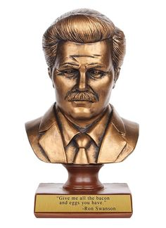 "Memorialize your never ending love for Parks and Recreation's Ron Swanson by bringing home this bust. The Ron Swanson Bust features the likeness of this great parks and recreation director and the quote ""Give me all the bacon and eggs you have."""