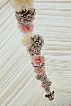 Suspend pink, ivory and latte pom poms alternating the colours across the length of a marquee for a pretty, romantic twist.