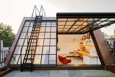 Glass workspace with garage- style wall of windows to get natural light and fresh air