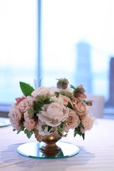 centerpiece in the RiverView Ballroom at the Cincinnati Marriott at RiverCenter, by wedding florist Floral Verde LLC in Cincinnati, Ohio; with pink hellebores, blush peonies, Brillant Stars Bridal spray roses, Keira garden roses, Quicksand roses, lily of the valley, white stock, Heuchera 'Vienna', Heuchera 'Dayglow Pink' and mini variegated pittosporum in a gold compote