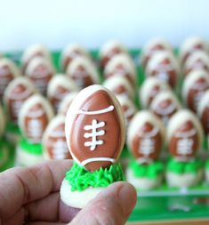 Kickoff {mini football} Cookie Bites by Munchkin Munchies.The grass was made with some thickened royal icing, tinted green (Wilton leaf green), and applied with a #233 Wilton grass tip. After the grass was applied, I immediately pushed a football (royal icing tinted with AmeriColor Chocolate brown) vertically into the middle, held it for a couple of seconds, and then it stayed put on its own.