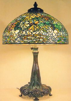 TIFFANY MAPLE LEAF TABLE LAMP 1900-1910 POSTCARD  The first Tiffany lamp was created around 1895. Beautiful in design and intricacy, each lamp was handmade by skilled craftsman, not mass or machine produced. Its designer was not, as had been thought for over 100 years, Louis Comfort Tiffany, but an unrecognized single woman named Clara Driscoll who was identified in 2007 by Rutgers professor Martin Eidelberg as being the master designer behind the most creative and valuable leaded glass…