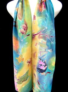 Silk Scarf Hand Painted Arabian Nights is unique piece of wearable art, vibrant and multicolored, Scheherazade telling her amazing 1001 stories to king, stories of Ali Baba and Aladdin, magic light and flying carpet, lost and hidden treasuries in the caves all under moon and stars of Arabian nights, images are outlined in silver.    This scarf you can wear or you can frame it, as you prefer.    Dimensions: 175x32 cm ( app. 69x12).  Material: 100% natural silk crepe de chine 14  Hand hemmed…