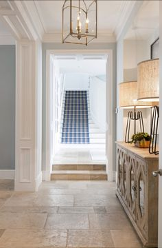 Hallway, staircase with runner, and French limestone floors.