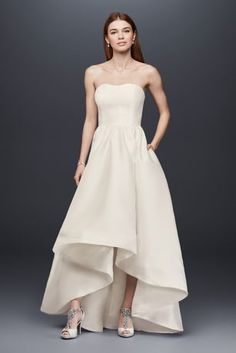 This lustrous mikado wedding gown is the epitome of effortless elegance. The simple bodice is even more lovely when topped with a sparkling sash, and the high-low hem shows off your dazzling heels.    DB Studio, exclusively at David's Bridal  Polyester  No train  Back zipper; fully lined  Dry clean  Imported  Shown with HJ13929 sash, not included