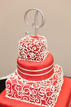 Bold Red Cake with alternating tier shapes and white swirl piping and a monogram topper.