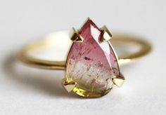 A watermelon tourmaline ring featuring what looks like suspended magical particles.