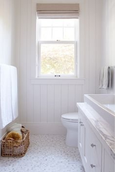 """Small Cottage with Neutral InteriorsThe walls are a T&G wood beadboard and the tile floor is: 5/8″ Mosaic Calacatta Gold Polished from """"Artistic Tile""""."""