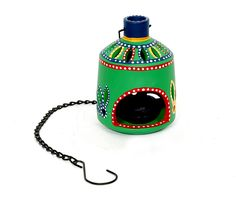 Bell-shaped, handpainted terracotta hanging tea light candle holder in Green colour featuring brightly coloured motifs and beautiful cut work, opening to place the tea light candles. Comes with a chain for hanging purpose. (There may be very minor variations in color combinations, between displayed and dispatched products, due to variety of artisans who handcraft the products. The look, feel and quality will , however, be consistent with what you see. That is an Indikala promise).