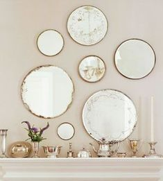 Mantel designs  A collection of antique mirrors creates a beautiful focal point over a fireplace mantel. The mirrors vary in size and quality, making the mix both romantic and unusual.  Budget Decorating Tip: Show off your collections. Silver tableware along the mantel complements the hanging mirrors. Unmatched sets of silver at garage sales and flea markets are usually inexpensive.