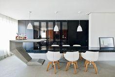 Sala de jantar: a mesa é um prolongamento da bancada de mármore e possui apoio metálico central. A mesa-bar, desenhada pelos arquitetos, é de concreto moldado na obra. Pendentes da Onlight. Cadeiras do designer Jean-Marie Massaud para Montenapoleone. (Foto: Maíra Acayaba)
