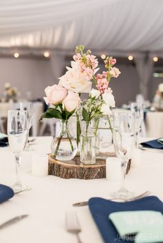 We love the DIY styling of this sweet centerpiece! All you need is an assortment of vases and glass bottles, a few small flowers of roses, baby's breath, or hyacinth, and a tabletop prop if you want to add a little extra to your centerpiece display!