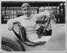 The racing legend, Kay Petre, in her car in the pits at Brooklands, prepares for her first drive since an accident on the circuit, ca. 1938.