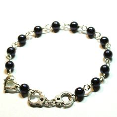 A pair of shiny silver handcuff charms in a bracelet of dark purple Swarovski pearls hand-linked in silver plated wire, finished with a heart shaped lobster clasp. Length is 7.   If you need a different length or would like a different color pearl, please ask. Heart shaped clasp can be replace...
