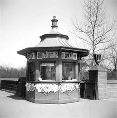 "New-Style Newsstand, 60th Street and Central Park West, April 12, 1937, by Alajos Schuszler ""Though the magazine covers may have become more provocative over time, those who frequent Columbus Circle will recognize the compact kiosk that has graced the subway entrance at the southwest corner of the park for more than 60 years."" ("