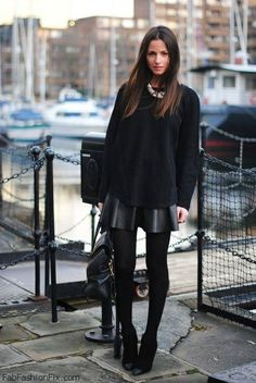 Black sweater and skater leather skirt for winter street style.