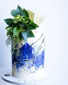 Don't Tell Charles blue and white watercolour cake with black paint splashes, white chocolate sail and greenery