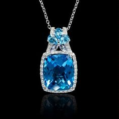 Pendant featuring six blue topaz 13.10ctw and two tanzanite stones .20ctw surrounded by round brilliants .36ctw in 18k white gold.