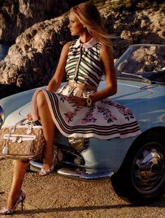 I want to be her. Wearing that dress. Holding that bag. Sitting on that car. Wearing those shoes. Staring off into the distance. Wind blowing in my hair. I want to be her.