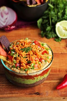 The BEST Vegan 7 Layer Dip - Homemade low-fat refried beans, creamy guacamole, zesty tomato salsa, hummus (no need for sour cream!), vegan cheese, and fresh chopped tomato & green onion! This easy dip is free of gluten and soy, and perfect for Grey Cup snacking! #vegan #glutenfree #greycup #gameday - ilovevegan.com