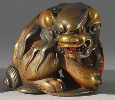 Lot 20: GOLD AND SILVER LACQUER NETSUKE By Masamitsu. In the form of a guardian lion protecting a brocade ball. - Eldred's | Invaluable
