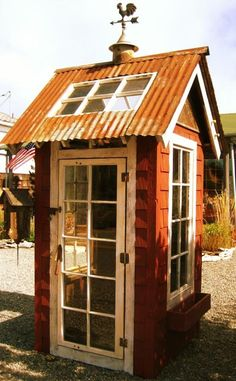 Garden shed with sheet metal roof and salvaged windows and door. What a cute shed!!