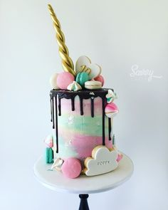 Unicorn cake with cookies, macarons and meringue kisses. Handpainted by Savvy Cakes