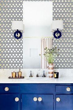 Bright bathroom with printed wallpaper and matching sconces