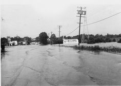 White Rock spillway  overflowed. This is looking up Garland Road from the Gaston Avenue interchange, Dallas, Texas. The train trestle has now been replacing with a walking trail. The actual spillway is beyond the trestle about a half block. Notice the Pig Stand sign on the left.  Photo probably taken between 1937 and 1939.