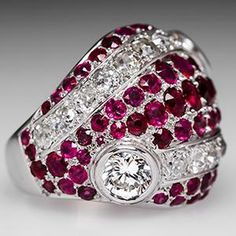 This stunning ruby and diamond cocktail ring features a round brilliant cut diamond bezel set to each side of the domed face of the ring. The brilliant cut diamonds are accented with round and cushion cut rubies as well as Old European cut diamonds, all pavé set into bands across the top. This vintage cocktail ring is in good condition but does show some abrasion to the rubies and abrasion/slight chips to the diamonds.