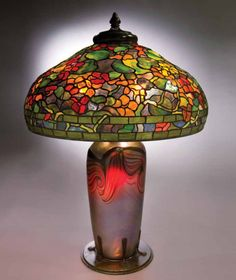 """""""Tiffany Studios Nasturtium Table Lamp This large, colorful lamp faithfully captures the beauty of the nasturtium blossoms and leaves. It is paired with a monumental blown favrile glass vase in which the glass is mounted in a heavy bronze bottom plate with tendrils rising up around the lower sections of the glass to securely hold the vase."""" Source:  http://www.michaans.com/"""