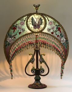 Antique hand-painted base has beautiful curves which complement the Celadon Chinoiserie Moon Lamp. The shade is hand dyed celadon green into plum and covered with antique fabrics including metallic lace, black netting which has a beautiful Chinoiserie pattern with birds and flowers on the sides. The lamp is overlaid on all panels with colorful antique floral appliqués. The shade has hand beaded fringe that adorns the bottom and lights up beautifully.