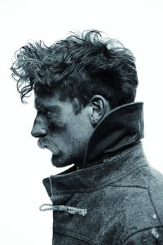 scruffy hair, mustache, toggle coat