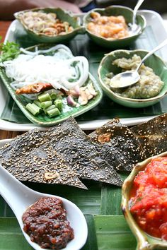 Traditional food from Laos including kaipen (river algae sheets), jaew (sweet and spicy sauce), eggplant dip, and rice vermicelli with condiments of coriander, peanuts, lemon grass and chilies.  -kc